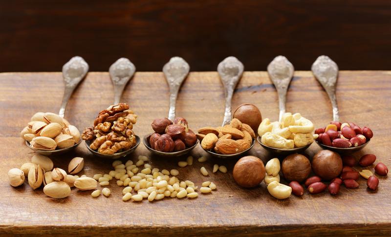 various kinds of nuts (cedar, cashew, hazelnuts, walnuts) in spoons
